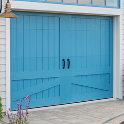 A blue barn style garage door made with composite wood materials.