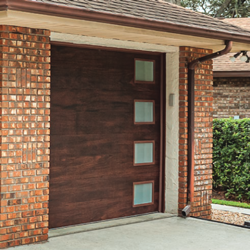 A contemporary style grage door with a flush wood panel design and a column of windows on the right hand side of the door.