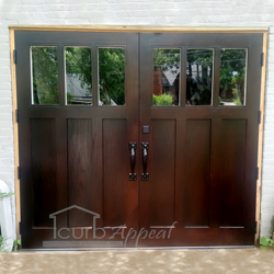 A handmade wood swing out garage door with a dark stained finish, handles, and a keylock.